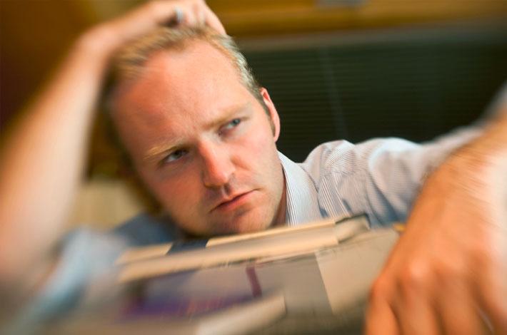 Auf dem Headerbild für Arbeitsrecht Duisburg ist ein verzweifelter Mann zu sehen, der über Unterlagen gebeugt ist.